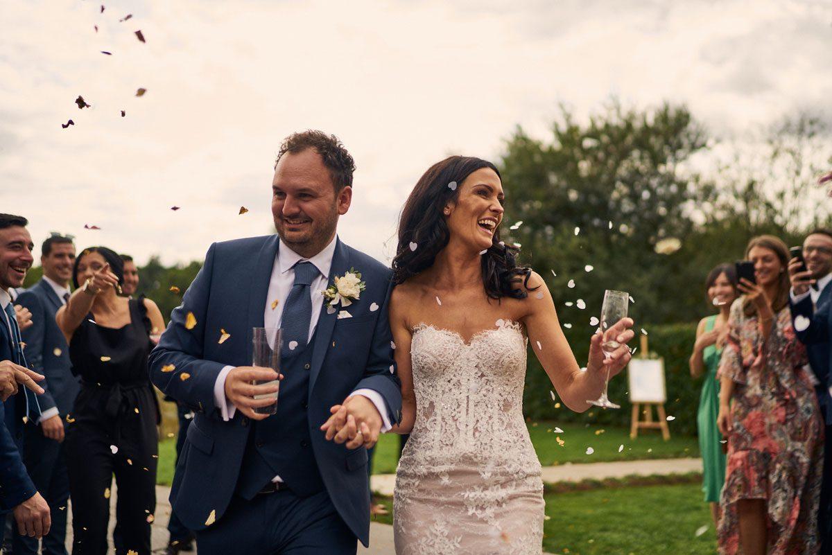 Bride & Groom walking through confetti on their  wedding breakfast
