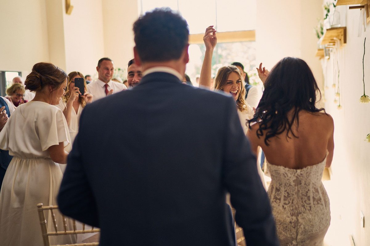 Bridesmaids cheering as Bride & Groom enter the room