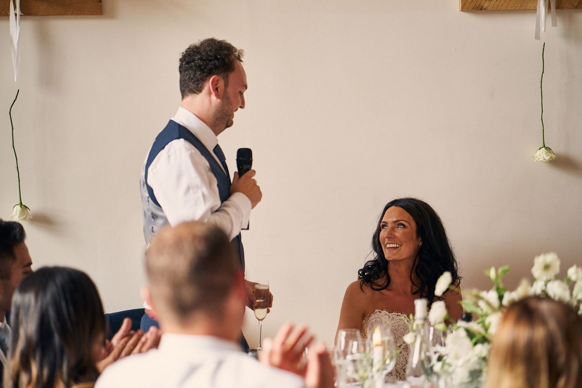 groom making his wedding speech looking lovingly at his new wife