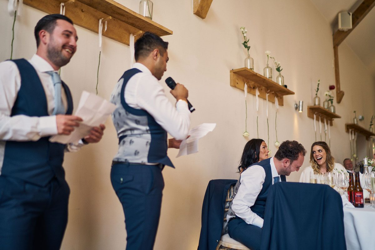 Bride & Groom laughing hard at the Best Man's speech