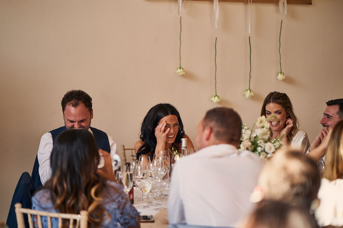 Bride covering her faced with embarrassment  as the Best Men make their speech