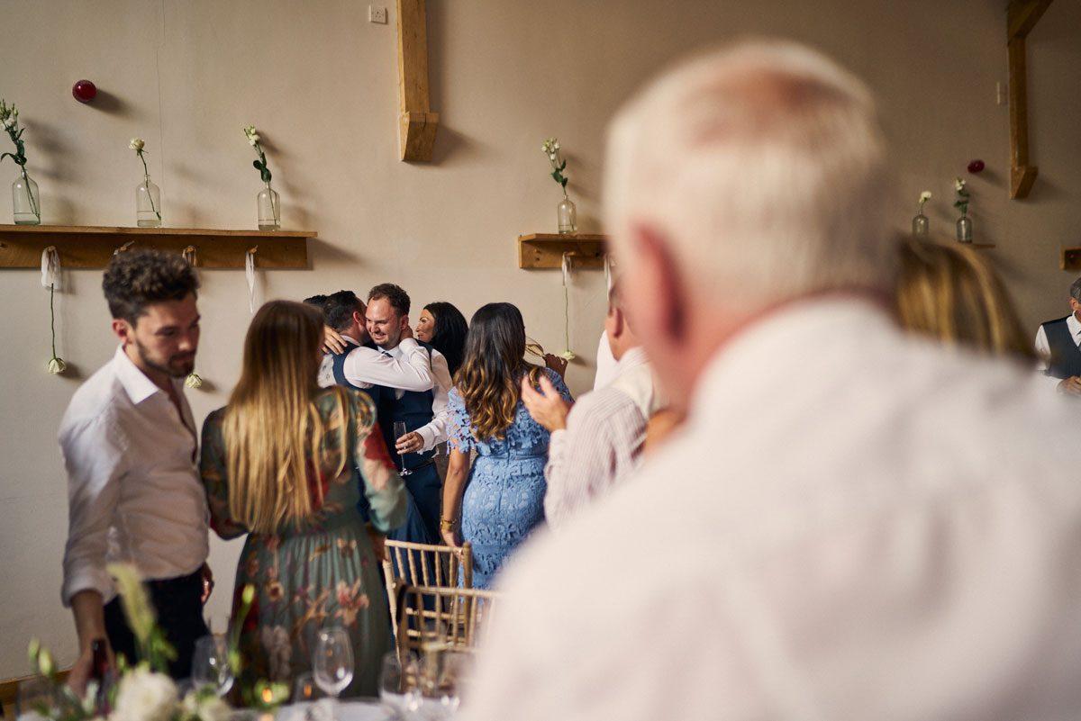 Bride & Groom hugging Best Man after their speech