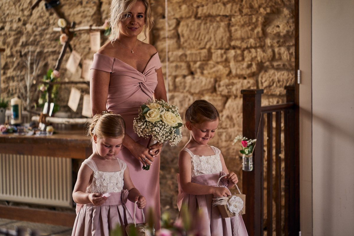 flower girls and bridesmaid walking down the aisle at the great tythe barn