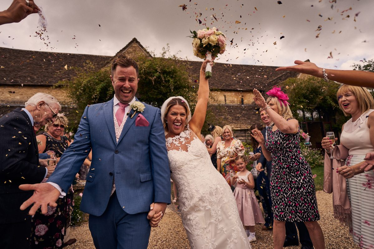 Confetti being thrown over bride and groom outside of The great tythe barn wedding venue