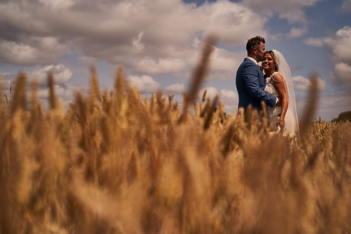 bride and groom having a romantic hug in the corn fields