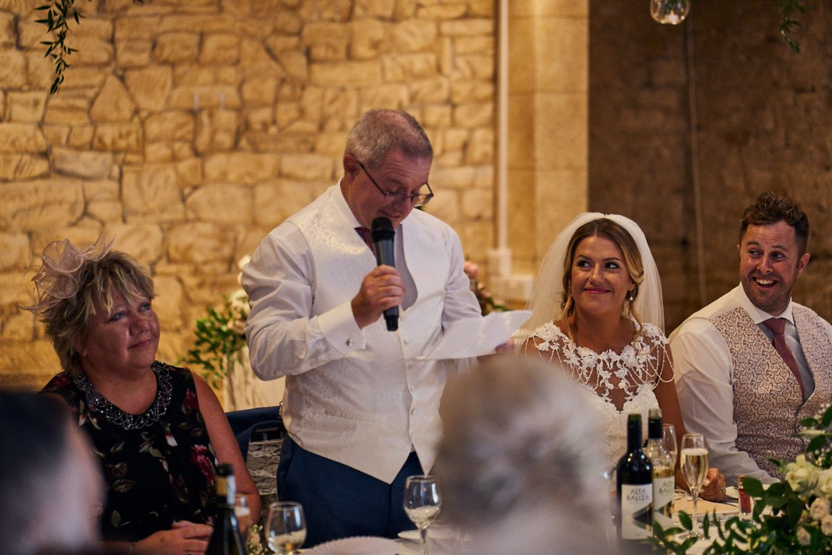 bride smiling at her dad's speech