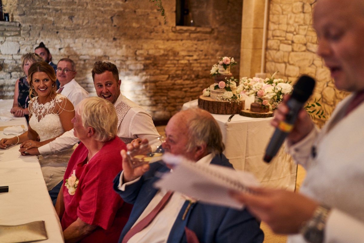 groom laughing at best man's speedch