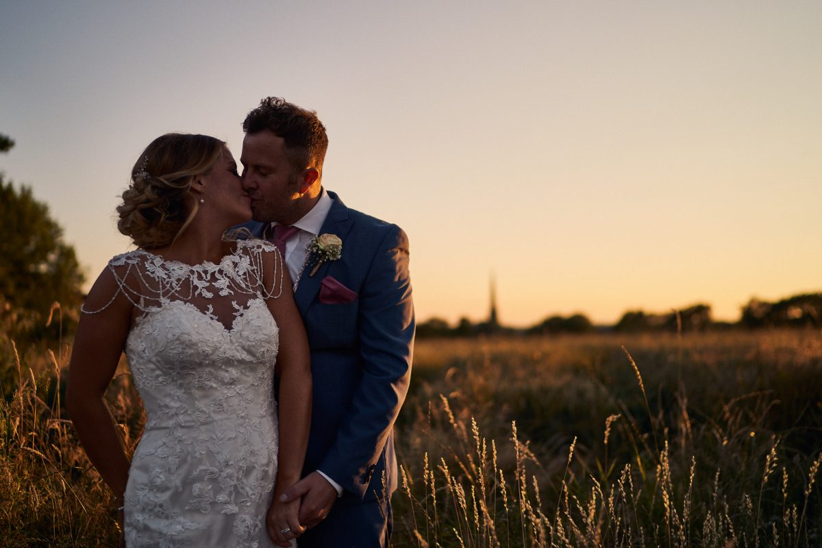 bride and groom kissing at sunset in the field