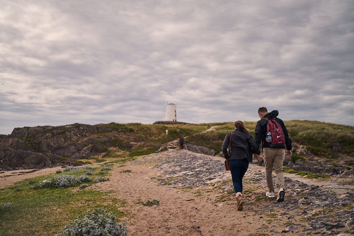 couple walking on Llanddwyn Island