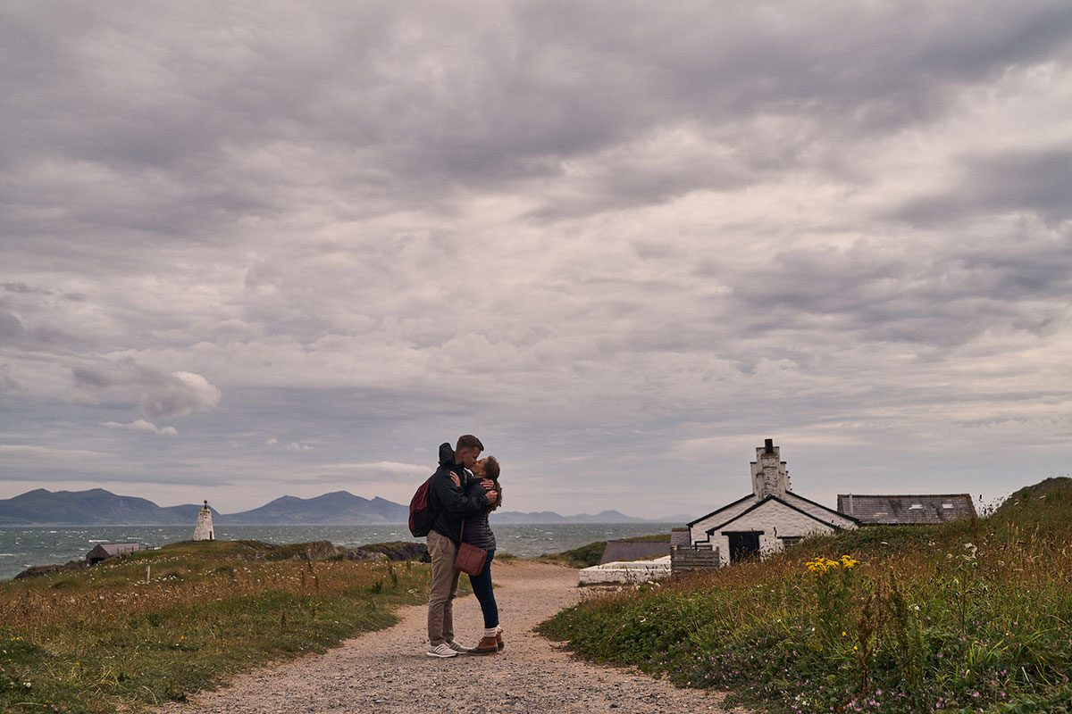couple hugging by the pilots cottages on Llanddwyn Island