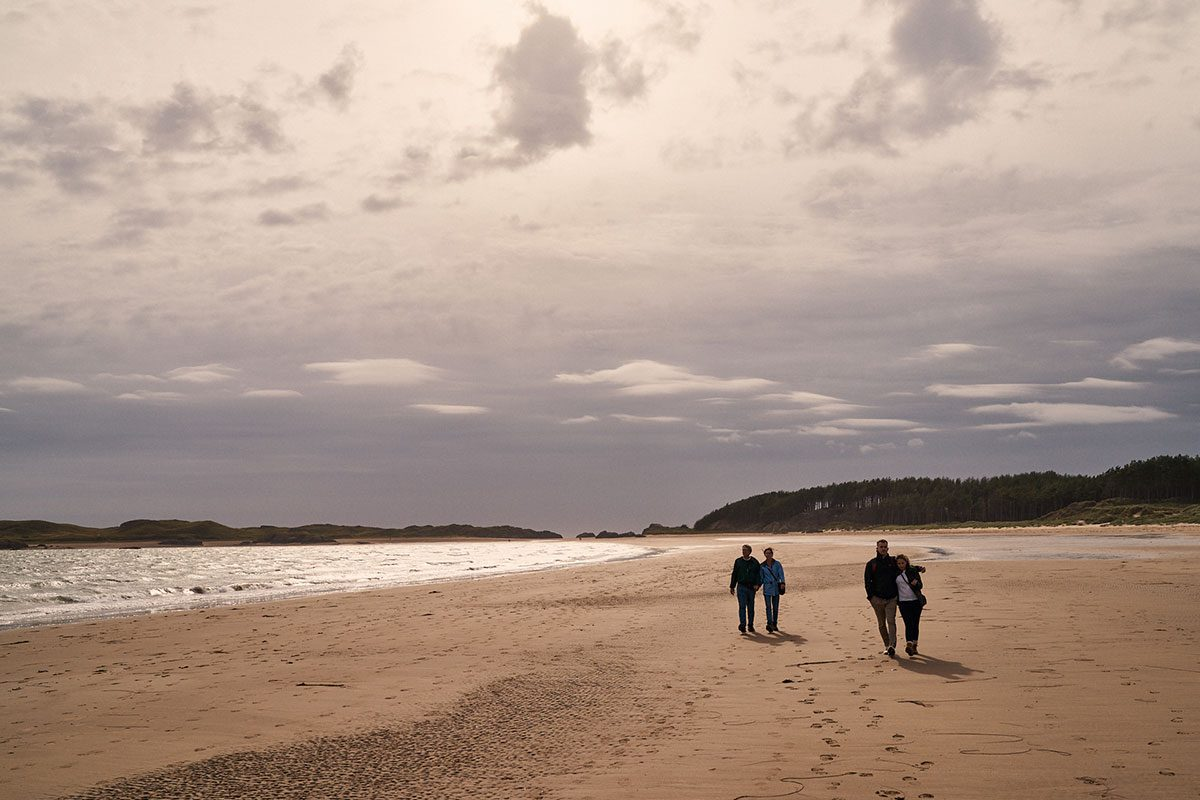 family walking along Newborough Beach, Anglesey