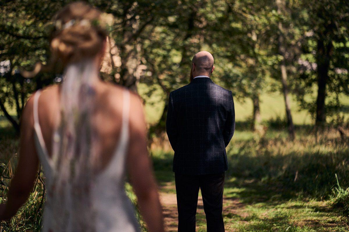 bride & groom first look before wedding in the woods