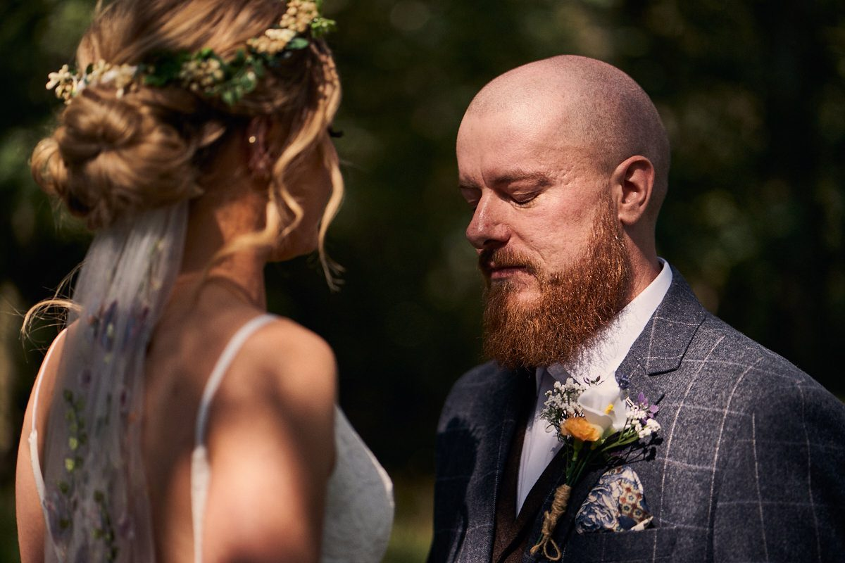 groom looking emotional when seeing his wife for the first time