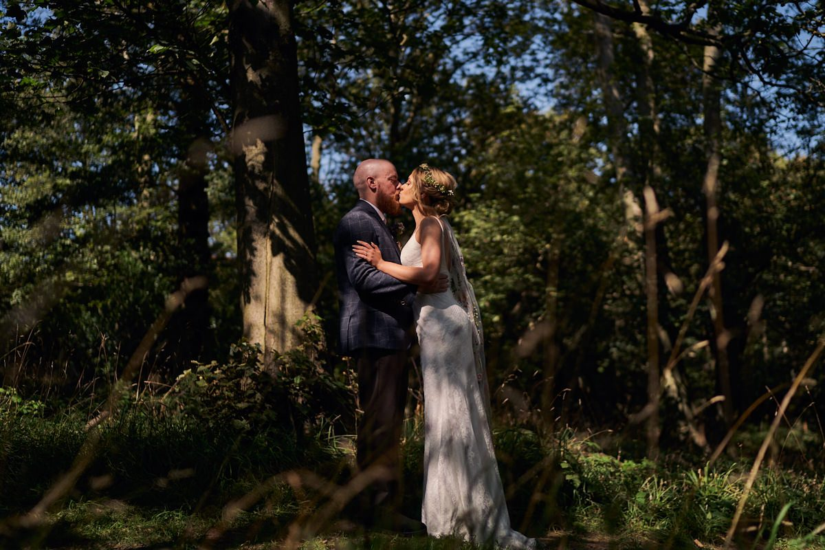 bride and groom kissing during first look in the forest