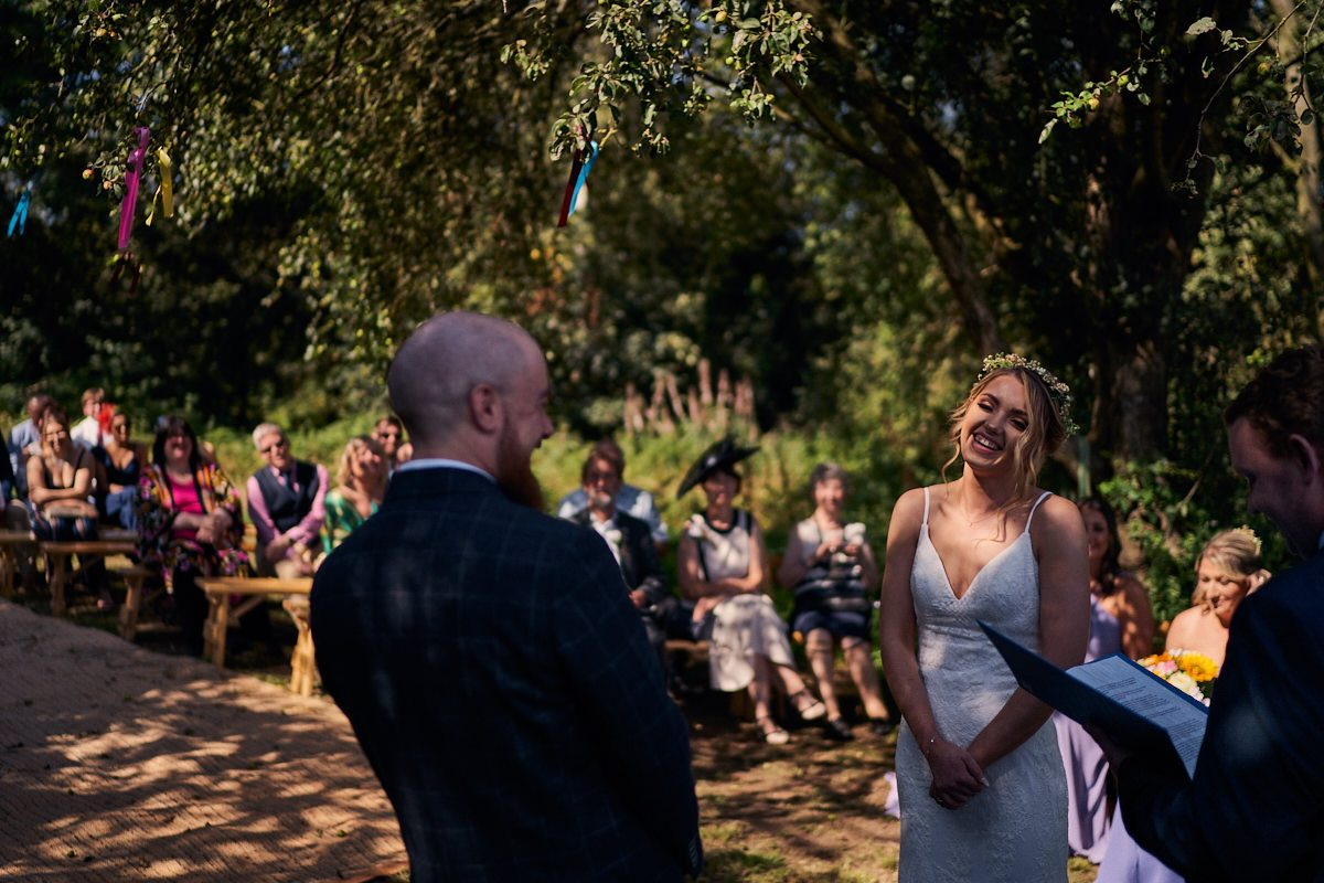 bride and groom laughing during outdoor wedding ceremony