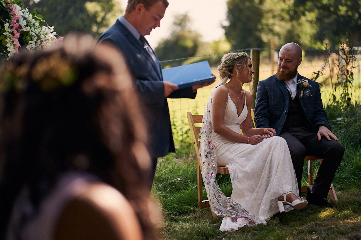 bride and groom sat down smiling at each other
