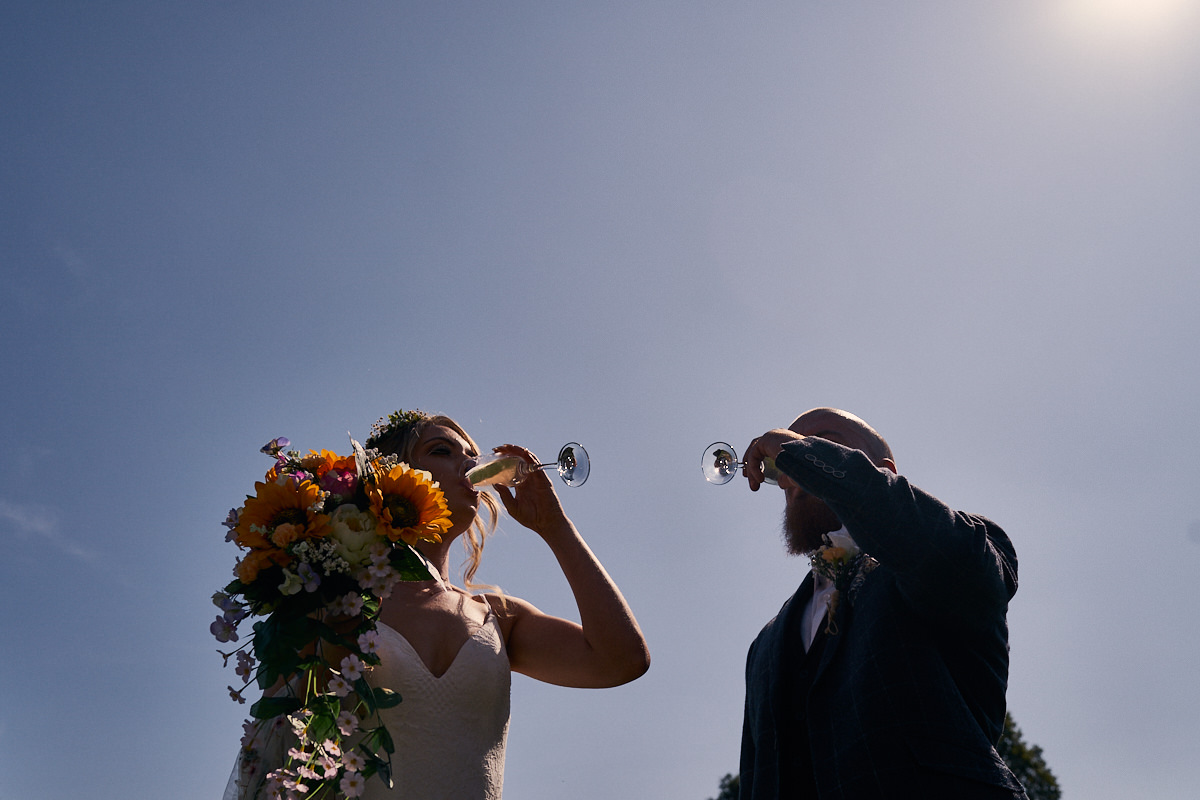 bride & groom drinking champagne on a sunny day