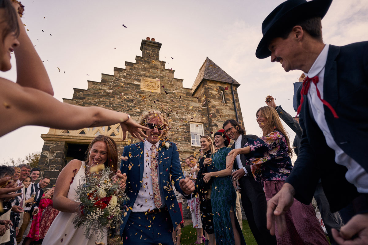 Weddings guests throwing confetti at Bride & Groom