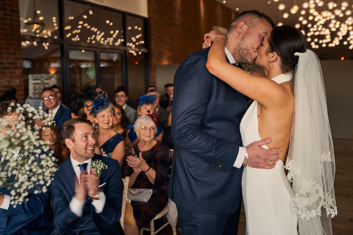 Couple having their first kiss as a married couple